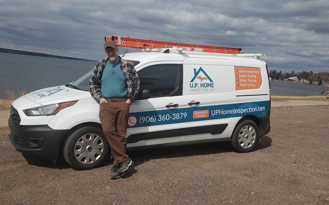 Picture of Marquette, MI home inspector Rich Beasley with his truck after a home inspection in L'Anse, MI