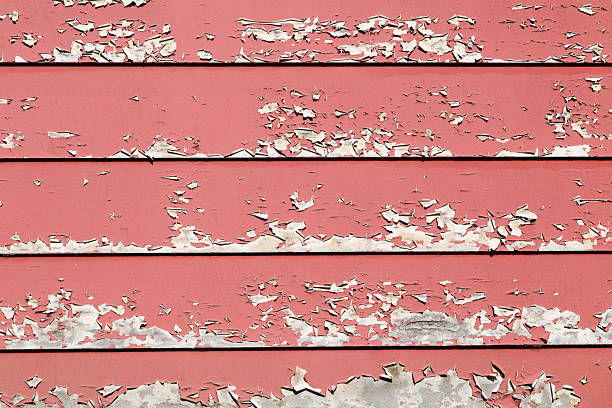 Masonite siding photographed during a home inspection in Marquette, MI, with cracked and peeling red paint.