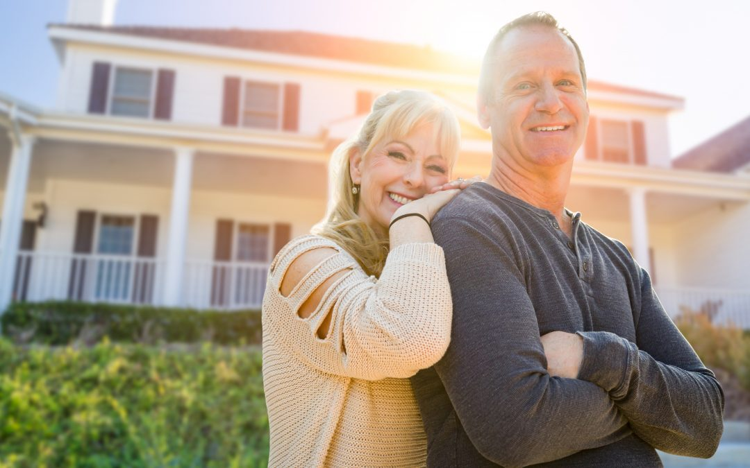 photo of a happy couple in front of a beautiful home