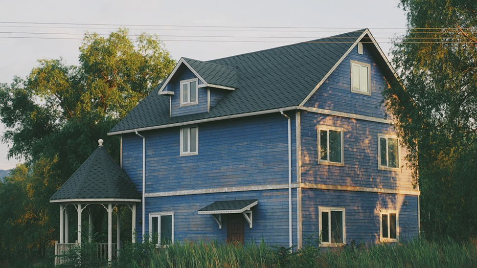 An old Victorian home with wood siding and shabby blue paint.